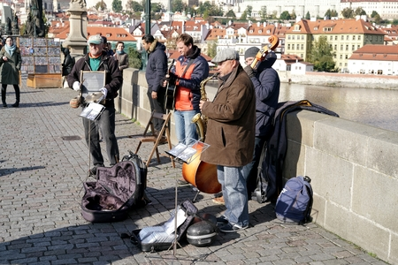 making music: PRAGUE, CZECH REPUBLIC OCTOBER 21, 2016: Street musicians on the Charles Bridge in Prague entertain the passing tourists with a concert