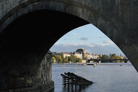 View under the Charles Bridge to Prague with the National Theatre in the center of the picture