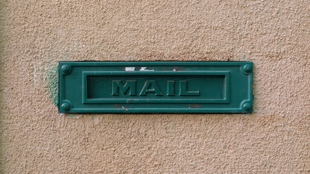 Green mailbox on the facade of a house Stock Photo