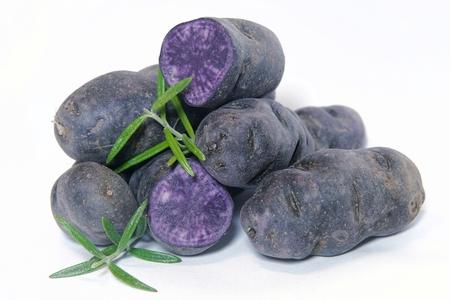Aardappelen van het ras Vitelotte op een tafel Stockfoto
