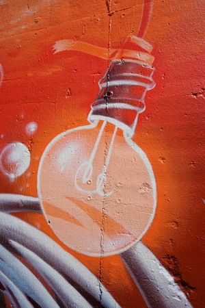 daubed: BERLIN, GERMANY � � MAY 10, 2016: Light bulb as a detail of a graffiti on a house wall in the center of Berlin