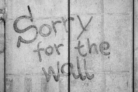 demarcation: Concrete wall with the words Sorry for the Wall Stock Photo