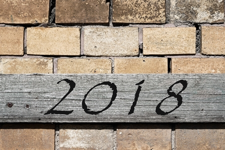 time specification: Wooden board on a house wall with a year 2018