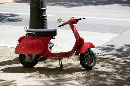 BERLIN, GERMANY - AUGUST 06, 2017: A red Vespa stands on the edge of the Kurfürstendamm in Berlin Редакционное