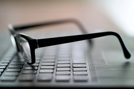 Glasses on the computer keyboard during a break Stock Photo