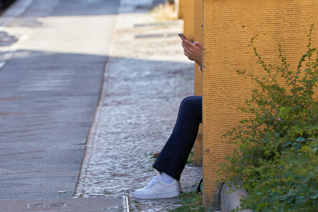 BERLIN, GERMANY - JUNE 07, 2018: Young woman sitting on a street in Berlin and typing on the smartphone Editorial