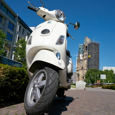 BERLIN, GERMANY - JUNE 08, 2016: Parked scooter in downtown Berlin. In the background, the Breitscheidplatz is the Memorial Church.