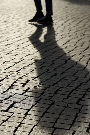 Shadow of a pedestrian in downtown Leipzig in backlight