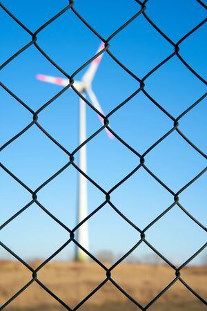 Wind turbine behind a fence in an industrial area in Magdeburg