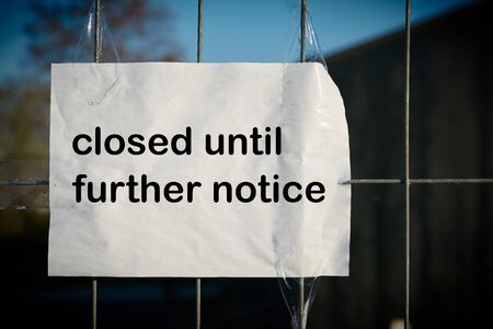 Sign on a fence with the inscription closed until further notice