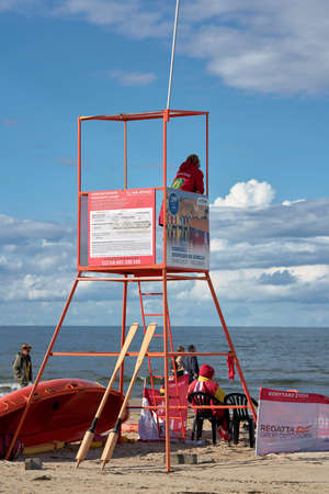 SWINOUJSCIE, POLAND - SEPTEMBER 06, 2020: Lifeguard with rescue tower on the beach of the Baltic Sea near Swinoujscie in Poland Редакционное
