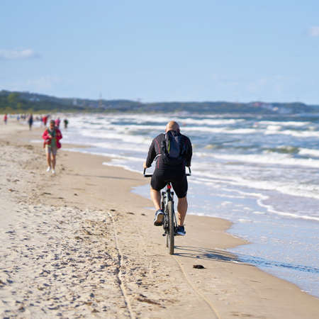 SWINOUJSCIE, POLAND - SEPTEMBER 10, 2020: Cyclist on the beach of Swinoujscie on the Polish Baltic Sea coast