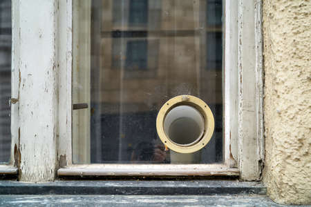 Ventilation hose of an air conditioner at the window of a dilapidated house in Prague
