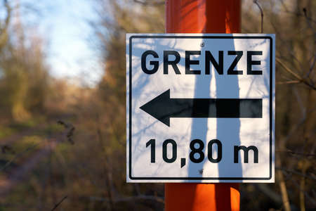 Sign with direction arrow and inscription border 10.80 meters at a forest road in Germany Standard-Bild