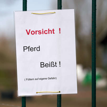 Sign on a fence in Germany with the inscription Caution horse bites, feeding at your own risk
