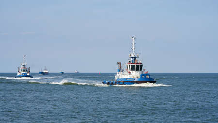 Swinoujscie, Poland - September 12, 2020: Tugboat escorting a ship on the way to the port of Swinoujscie on the Polish coast of the Baltic Sea