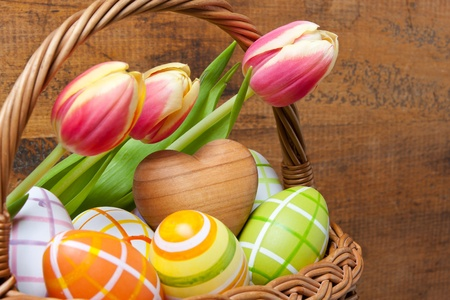 Basket with easter eggs and tulips in front of wooden background Stock Photo - 12669036