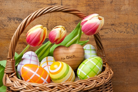 Basket with easter eggs and tulips in front of wooden background photo