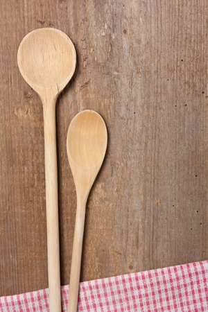 Two wooden spoons and dish towel laying on a wooden plank photo