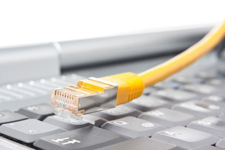 Macro of a yellow network cable in front of a keyboard Stock Photo - 13139708
