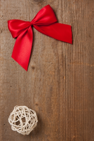 Wooden board with red ribbon and straw ball photo