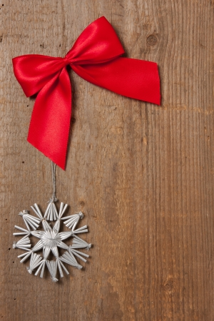 Rustic wooden board with red ribbon and silver star photo