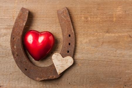 herradura: Corazón rojo y una herradura sobre una tabla de madera