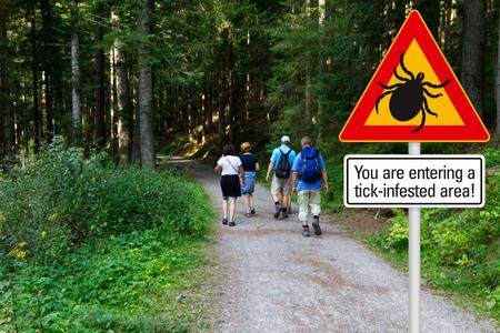 Señal de advertencia, cuidado con las garrapatas en el área infestada en el bosque verde con excursionistas Foto de archivo