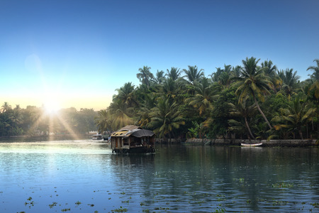 sunrise at backwaters landscape with swaying coconut trees and traditional house boats in Alleppey, Kerala, India Stock Photo