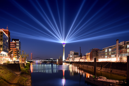 Panoramic skyline view of Dusseldorf, Germany at night with illuminated rhine tower in media harbor district Stock Photo