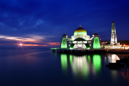 Glowing Strait Mosque of Malacca during sunset and blue hour. The so called swimming Mosque is located at the Historical Malacca City, Malaysia. Stock Photo
