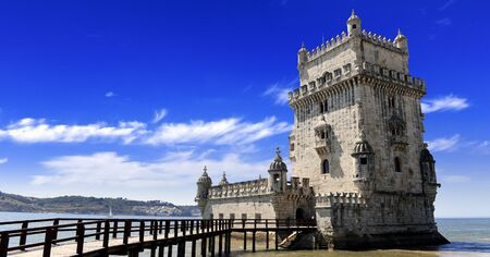 Scenic Belem tower and wooden bridge mirco with low tides on Tagus River. Torre de Belem is Lisbon's most visited tourist attraction in Lisbon, Belem District, Portugal