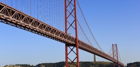 The April 25 Bridge on the left bank of the Tagus River, the monument of Cristo The river overlooks the river from a pedestrian tower on the south bank, Portugal