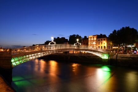 Dublin, Ireland. Night view of famous illuminated Ha Penny Bridge in Dublin, Ireland at sunset