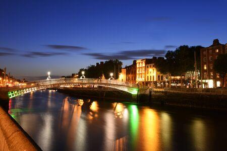 Dublin, Ireland. Night view of famous illuminated Ha Penny Bridge in Dublin, Ireland, at sunset