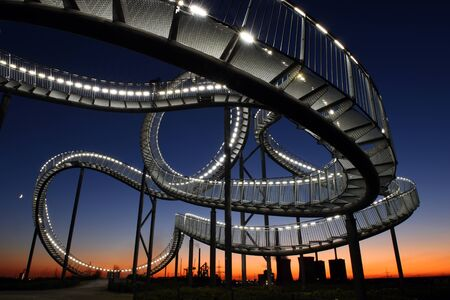Tiger and turtle construction while sunset, illuminated gangway in Duisburg, Germany