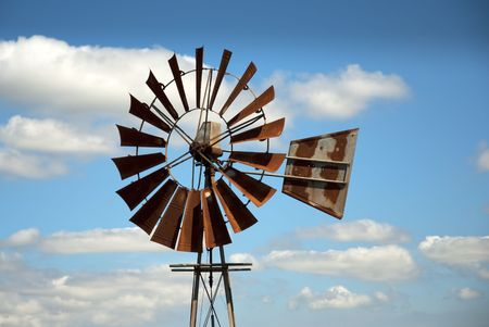 Rusty windmill with clouds in the background photo