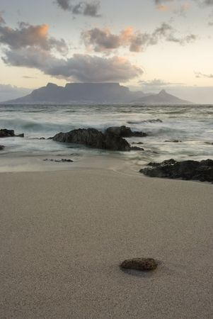 Table mountain with beach and rocks in the foreground