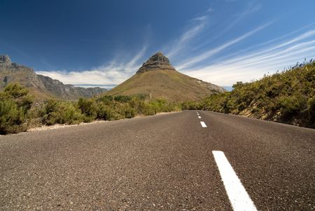 Road leading toward a mountain in the background with blue sky and clouds photo