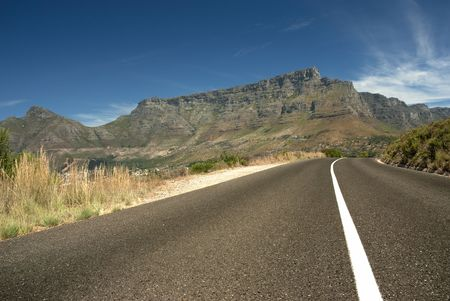 Road leading toward Table mountain in the background with blue sky and clouds photo