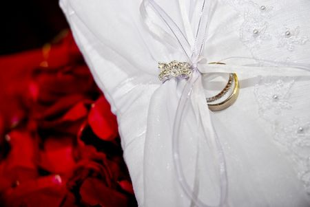 Wedding ring on a white cushion with red rose petals in the background