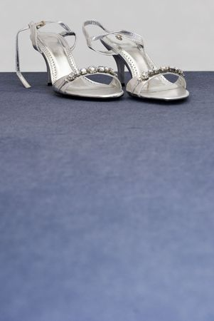 Silver formal wedding shoes at top of frame with blank bue space below Stock Photo