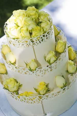 desert rose: White three-tiered wedding cake decorated with light yellow roses