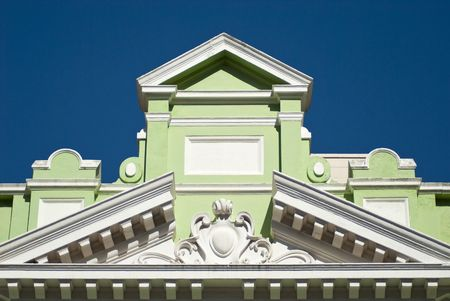 Top decorations of an old green and white building with blue skies in the background photo