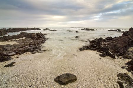 beack: Wide shot of a very rocky beack with stormy clouds overhead. A single round rock in the foreground Stock Photo