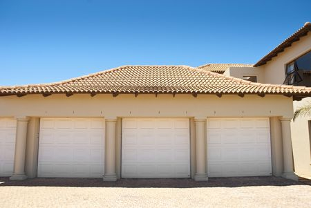 White triple garage doors with blue blue skies above and driveway in the foreground photo