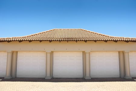 White triple garage doors with blue blue skies above and driveway in the foreground