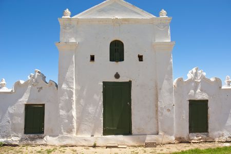 Old white building with green doors and clear blue skies above
