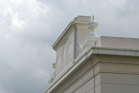 Roof top of classic building with fine details and stormy clouds above