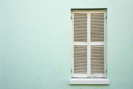 White, closed window shutters in a light green wall, framed on the right Stock Photo - 6232116